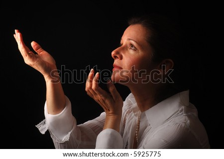 Beautiful woman praying, with light from above - stock photo