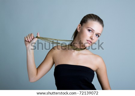 Beautiful woman pulling long necklace. Gold jewelry - stock photo