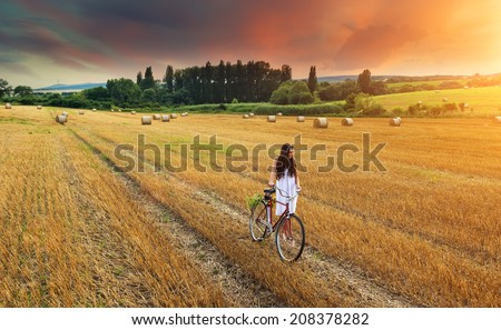 Beautiful woman pushes old red bike in a wheat field - stock photo