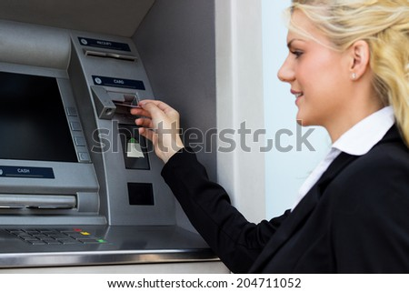 Beautiful woman put her credit card at the ATM