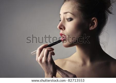 Beautiful woman putting on some lipstick - stock photo