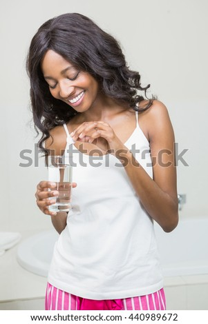Beautiful woman putting pill in to a glass of water in the bathroom - stock photo