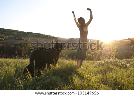 Beautiful woman raises her arms to the sun in joy whilst walking her dog - stock photo