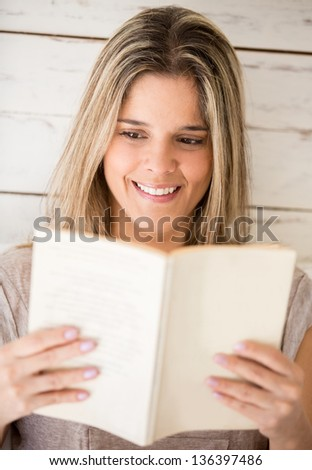 Beautiful woman reading a book and smiling - stock photo