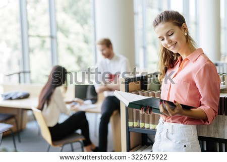 Beautiful woman reading a book in a library and thinking