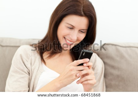Beautiful woman reading a message on her mobile phone in the living room
