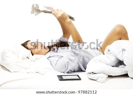 beautiful woman reading newspaper over her head on white background - stock photo