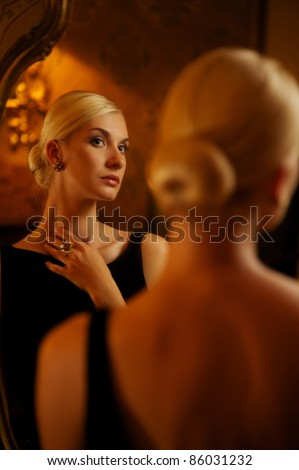 Beautiful woman reflected in vintage mirror - stock photo