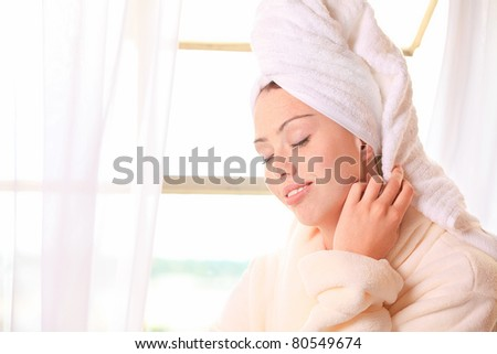 Beautiful woman relaxes by the window at a spa - stock photo