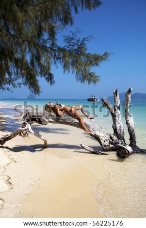 Beautiful woman relaxes on a tree in paradise. - stock photo