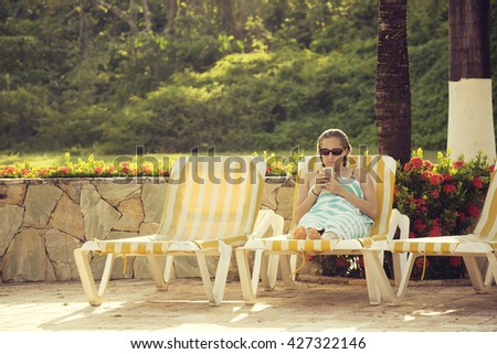 Beautiful woman relaxing and checking her cell phone at a tropical island resort