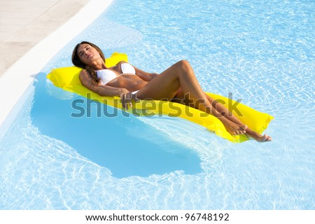 Beautiful woman relaxing and floating on pool, high angle view - stock photo