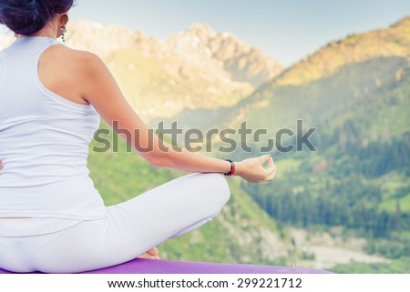 Beautiful woman relaxing and meditating outdoor at swiss mountain. She sits at peak of mountain in lotus position and feel harmony of your body and nature. Healthy lifestyles concept of body and soul