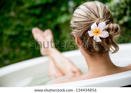 Beautiful woman relaxing at home and taking a bath - stock photo