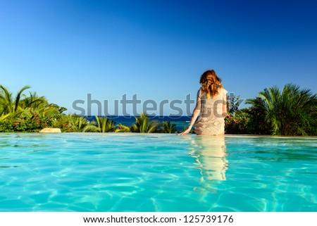 Beautiful woman relaxing at swimming pool - stock photo
