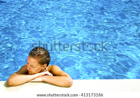 Beautiful woman relaxing at Swimming Pool in summer day