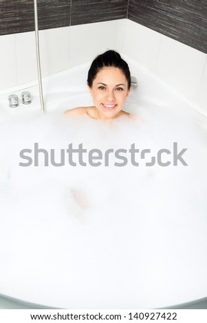 Beautiful woman relaxing in bath smile, young girl bathing in bathtub jacuzzi with foam top angle view - stock photo