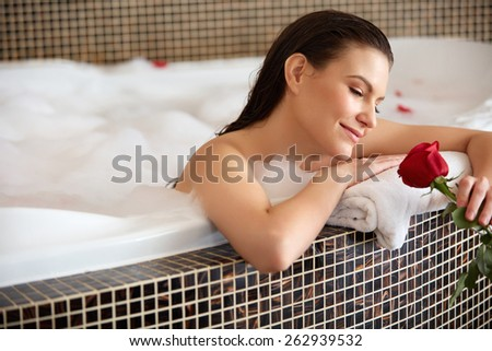 Beautiful Woman Relaxing in Bath With Rose. Body Care - stock photo