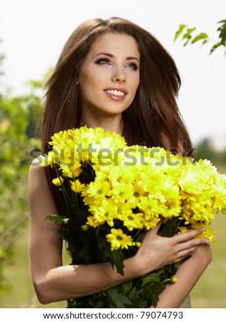 Beautiful woman relaxing in flower field - stock photo