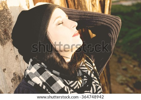 Beautiful woman relaxing in woodland standing leaning against the trunk if a tree with her eyes closed in enjoyment and bliss