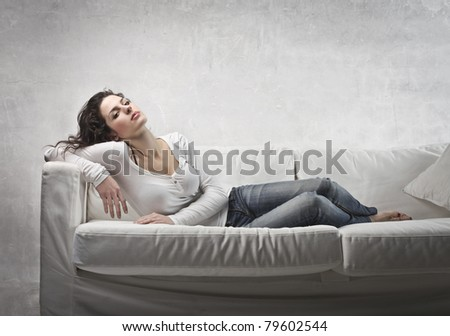 Beautiful woman relaxing on a sofa - stock photo