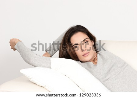 Beautiful woman relaxing on sofa at home - stock photo