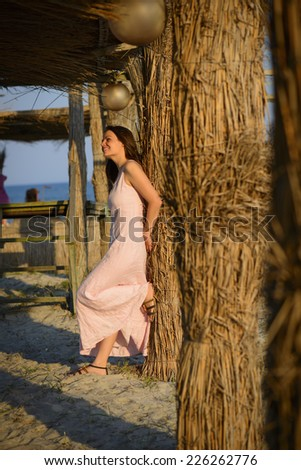 Beautiful woman relaxing on the beach on sunset. Full Length Portrait of a beautiful young woman on the beach. - stock photo