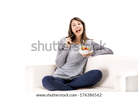 Beautiful woman relaxing on the sofa and eating a fruit salad - stock photo
