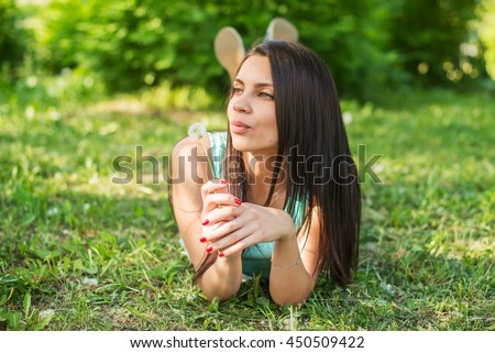 Beautiful woman relaxing outdoors on grass looking happy and smiling