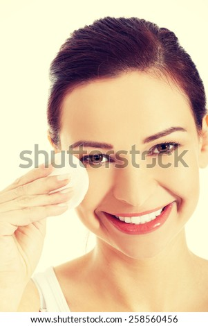Beautiful woman removing face makeup with cotton pad. - stock photo