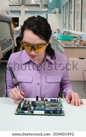Beautiful woman repair soldering a printed circuit board - stock photo