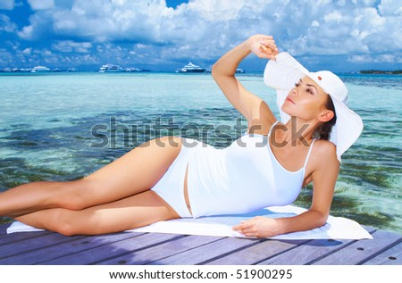 Beautiful woman resting near water at Maldives - stock photo