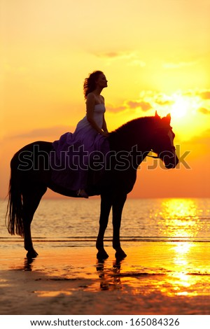 Beautiful woman riding a horse at sunset on the beach. Young beauty girl with a horse in the rays of the sun by the sea. - stock photo