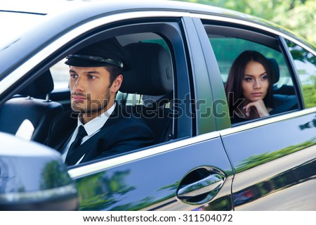 Beautiful woman riding in a car with chauffeur - stock photo