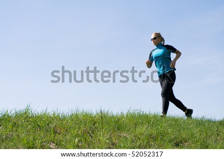 Beautiful woman runner training outdoors over blue sky