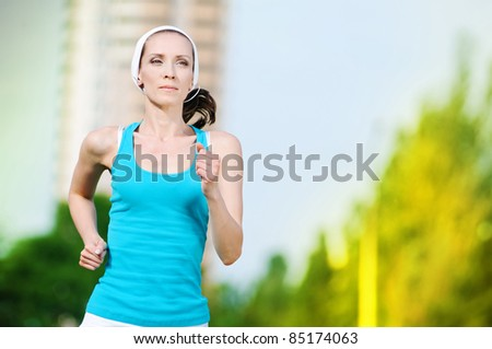Beautiful woman running in green park on sunny summer day - stock photo
