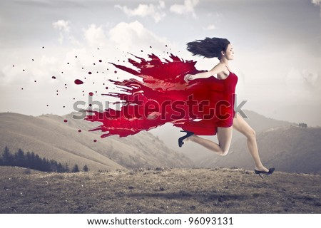 Beautiful woman running with her dress melting in red paint - stock photo