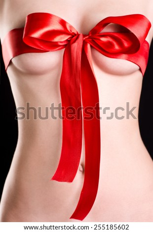 Beautiful woman's breasts in bow - stock photo