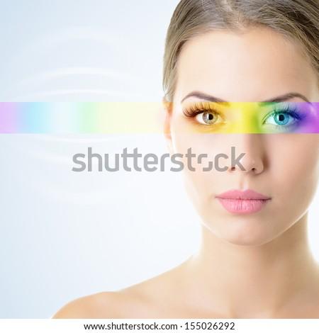 beautiful woman's face with rainbow light on eyes - stock photo