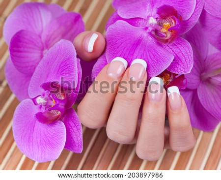 Beautiful woman's hand with perfect french manicure holding purple orchid flowers on bamboo background