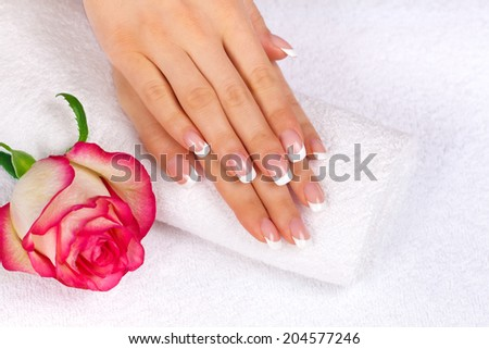Beautiful woman's hands with french manicure and rose on towel
