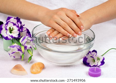 Beautiful woman's hands with perfect french manicure in bowl of water decorated with flowers - stock photo