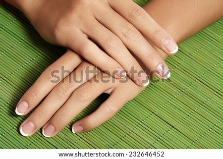 Beautiful woman's nails with perfect french manicure on bright green natural bamboo. Care for female hands
