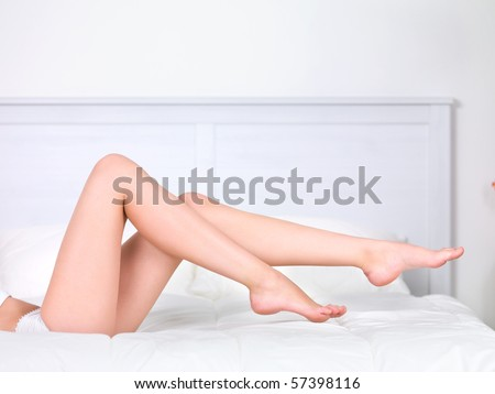 Beautiful woman's perfect clean legs on the bed - indoors - stock photo
