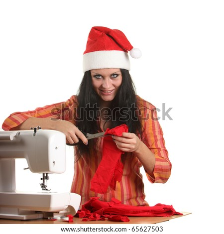 Beautiful woman seamstress in a christmas hat cut red cloth by scissors - stock photo