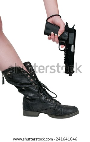 Beautiful woman shooting herself in the foot. - stock photo