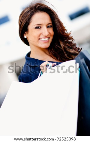 Beautiful woman shopping holding her purchases and smiling - stock photo