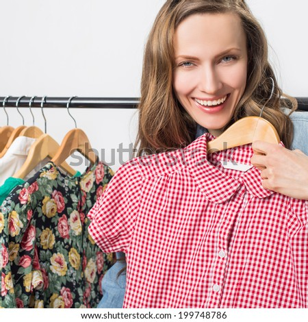 Beautiful woman shopping in clothing store over light grey background - stock photo