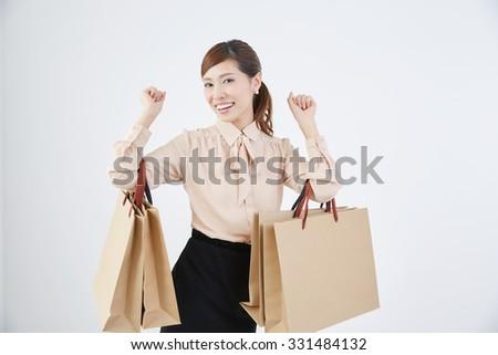 Beautiful woman shopping on white background - stock photo