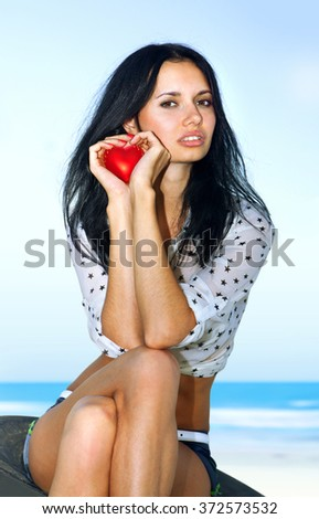 beautiful woman shows red heart in hands - stock photo